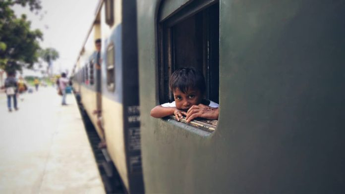 How to get from Varanasi to Nepal by public transport. Indian boy is looking out of a train.