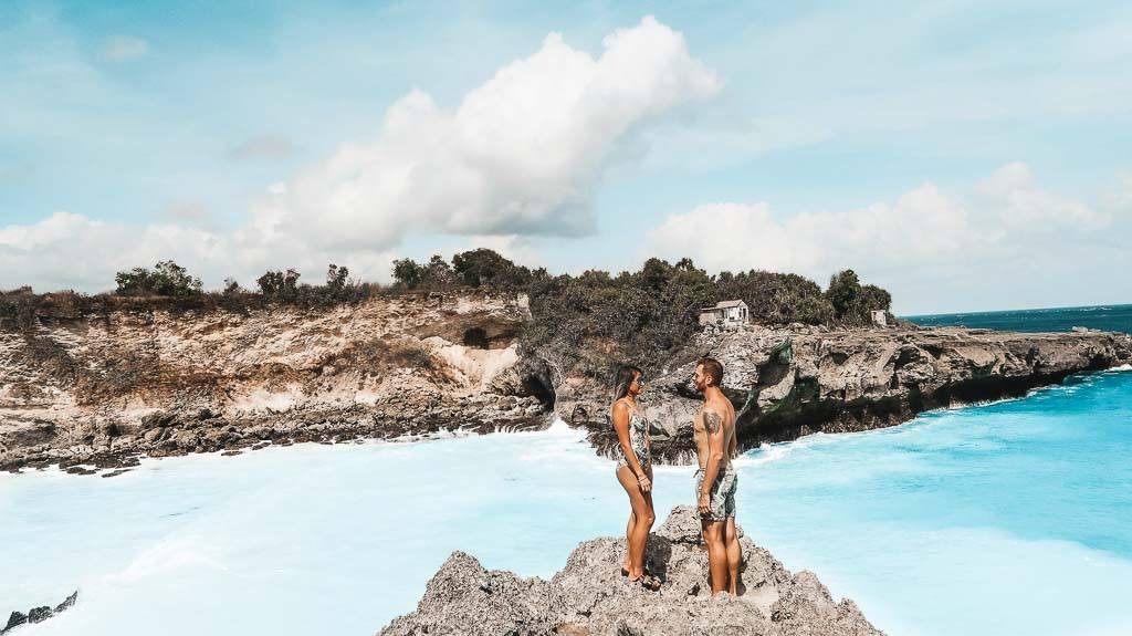 a couple is standing at the blue lagoon on Nusa Penida Indonesia.