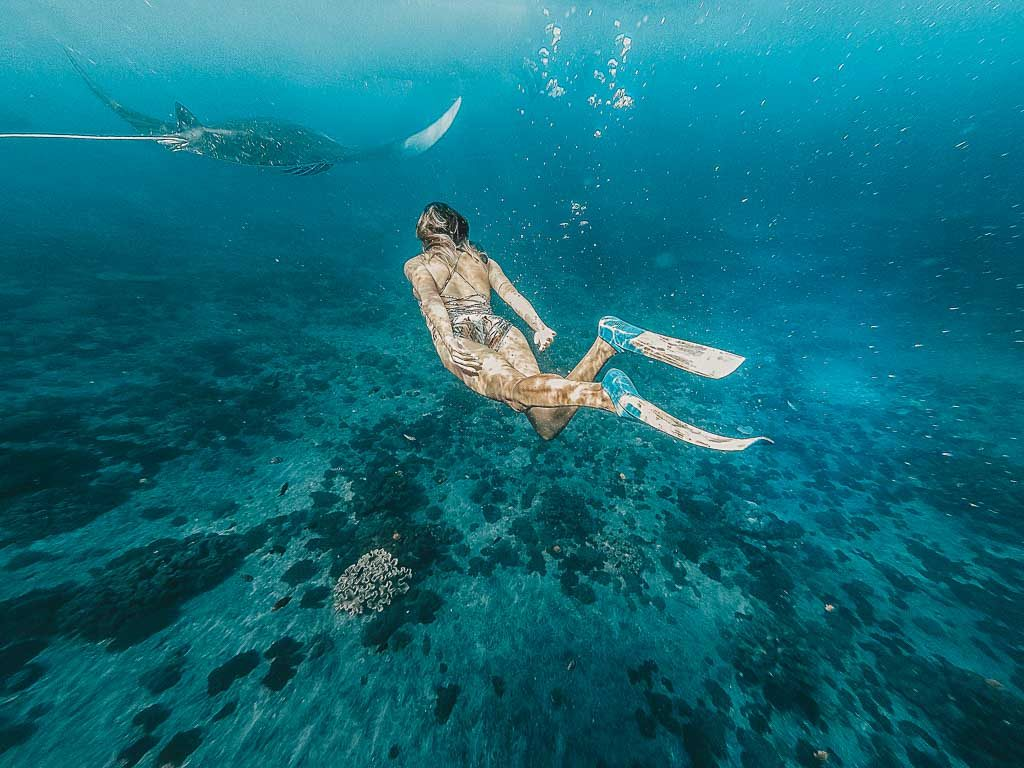 The Nusa Islands Top 5: a girl is snorkeling with a manta ray at Nusa Penida Indonesia