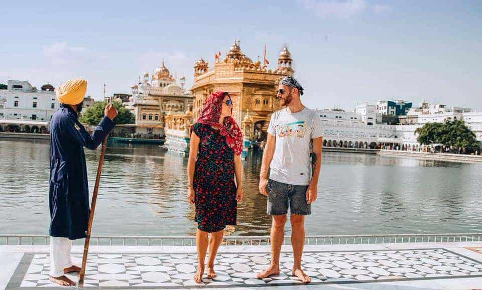 A couple is standing with a Sikh guard in front of the Golden Temple.