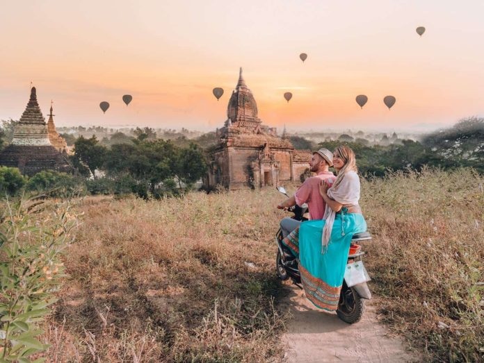 A couple sitting on a scooter in front of two pagodas in Bagan Myanmar and in the sky there are hot air balloons.