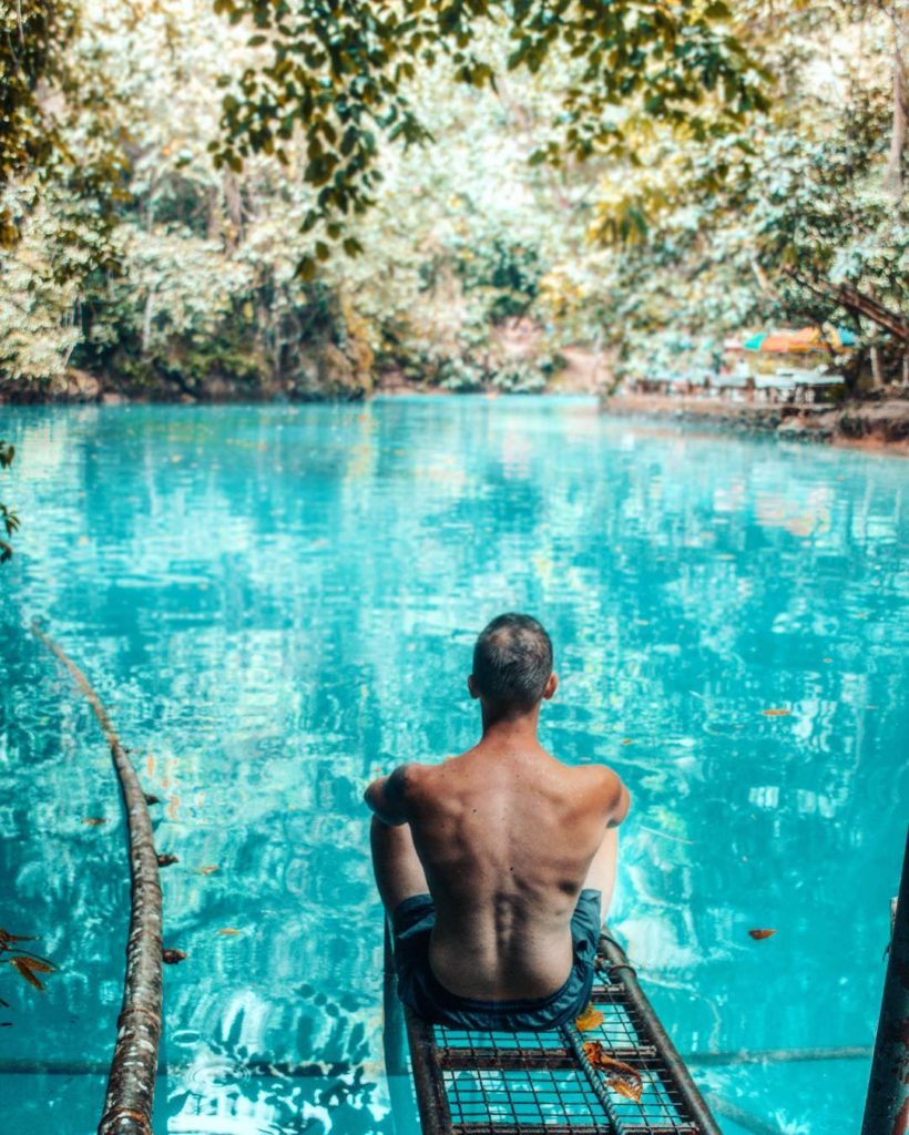 The best things to do in the Philippines: A men is sitting in front of a bue water basin.