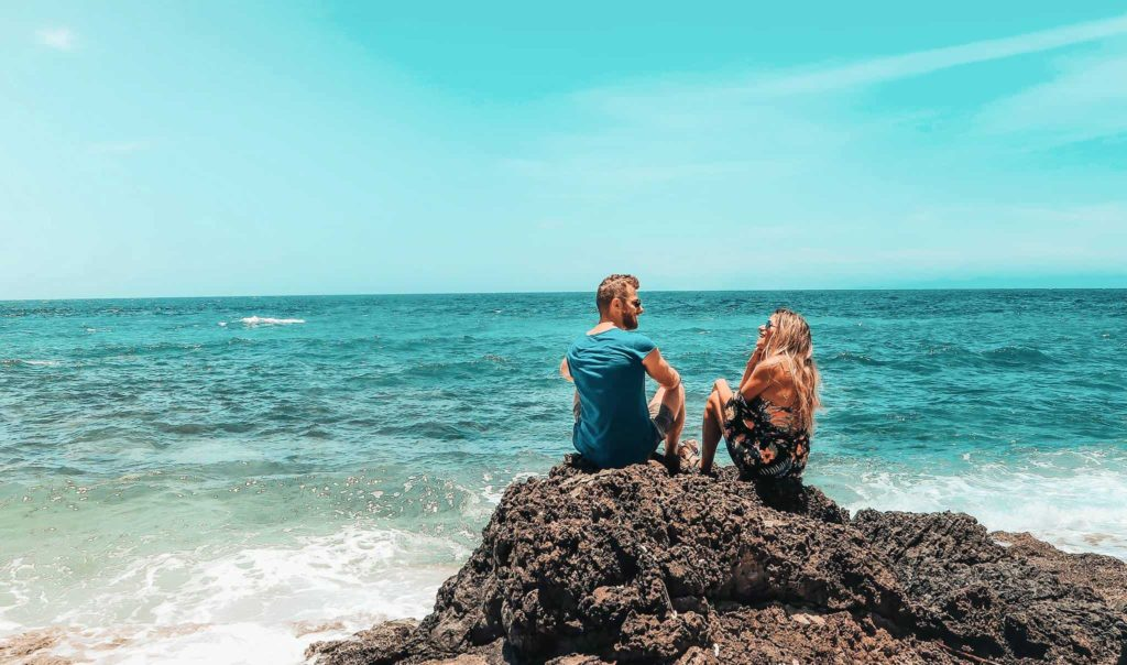 The best things to do in the Philippines a couple is sitting on a rock in front of the ocean.