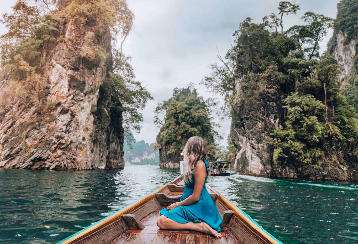 girl on boat with limestone mountains in the background Khao Sok Thailand