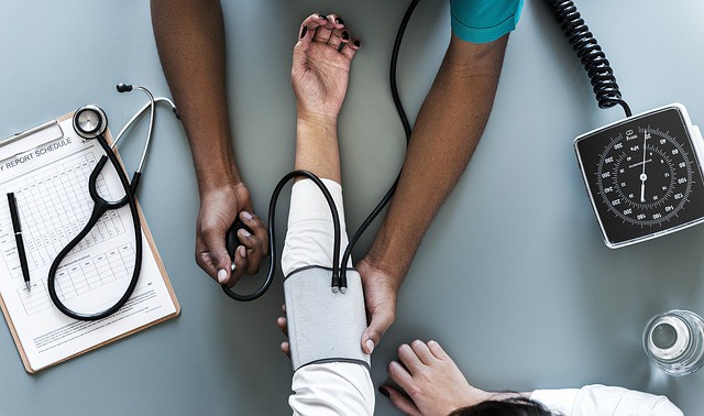 Do I need a travel insurance? A white person is gets the blood preasure checked by a black skined doctor