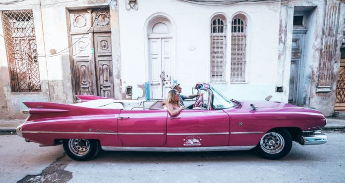 A couple in a pink Cadillac in the streets of Havana Cuba.