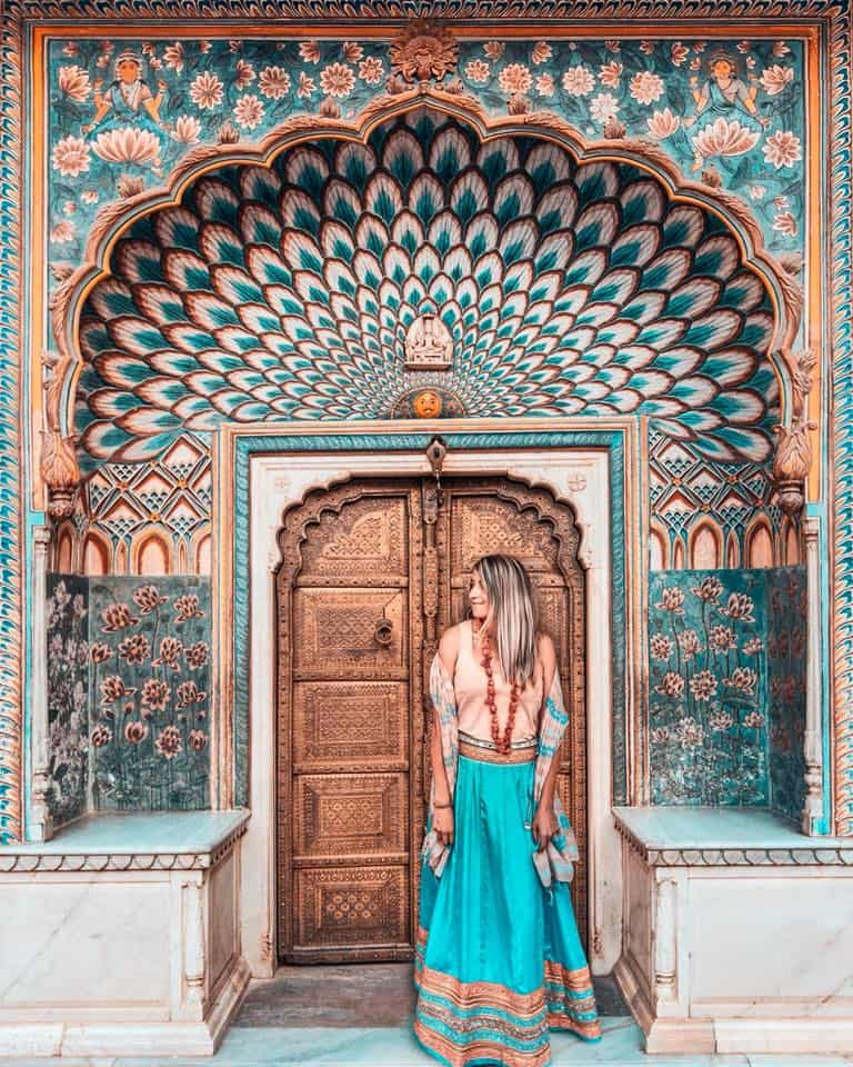 A girl is standing in front of a colorful doorway in Jaipur India.