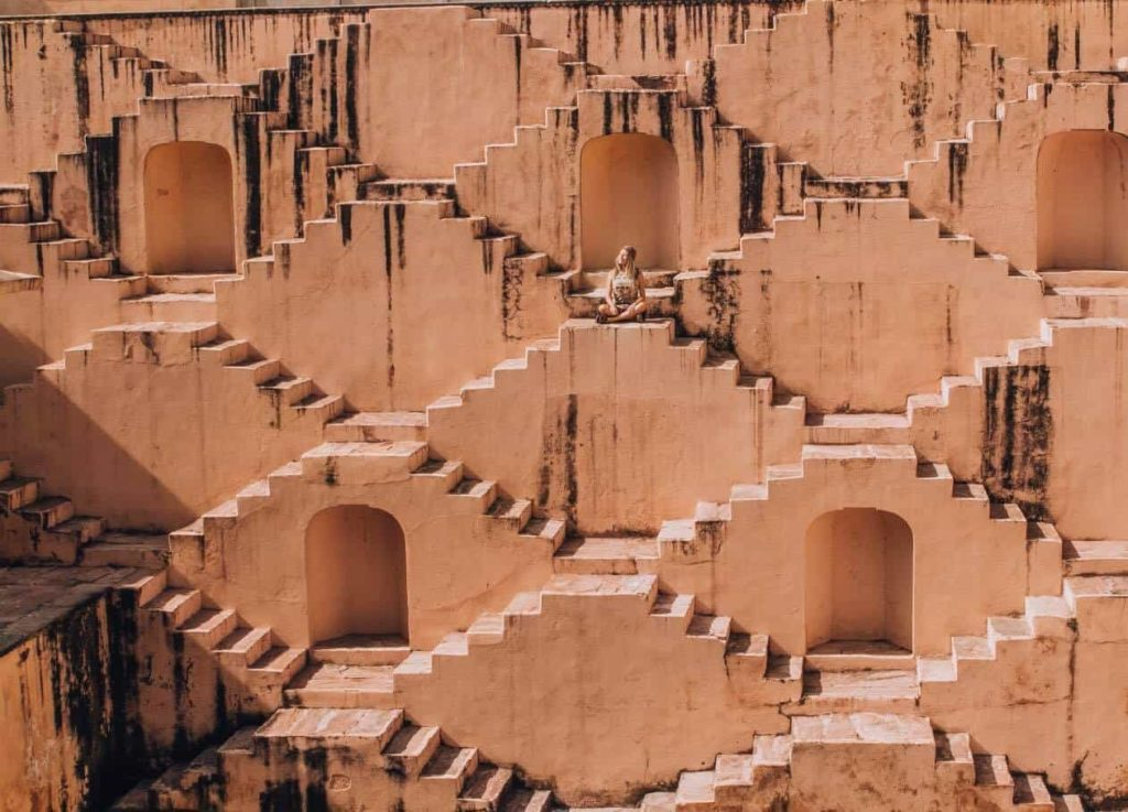 A girl is sitting on the stairs of the step well of Jaipur India.