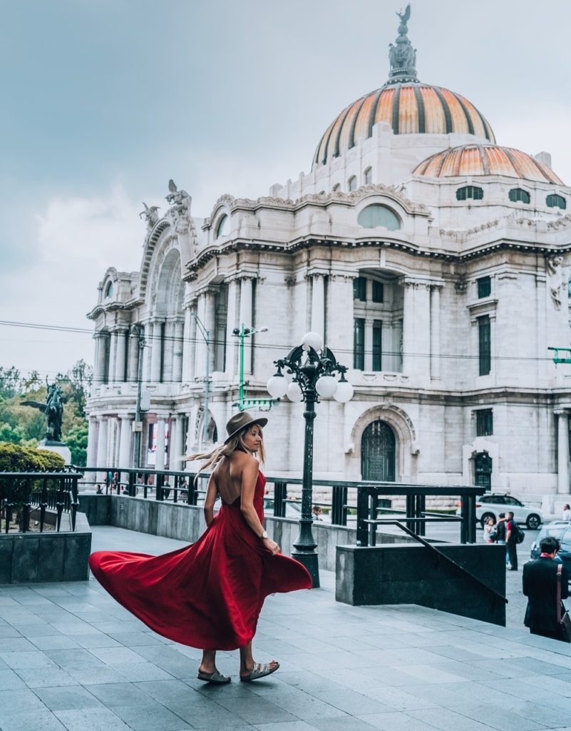 A girl is spinning in her red dress in front of a beautiful building