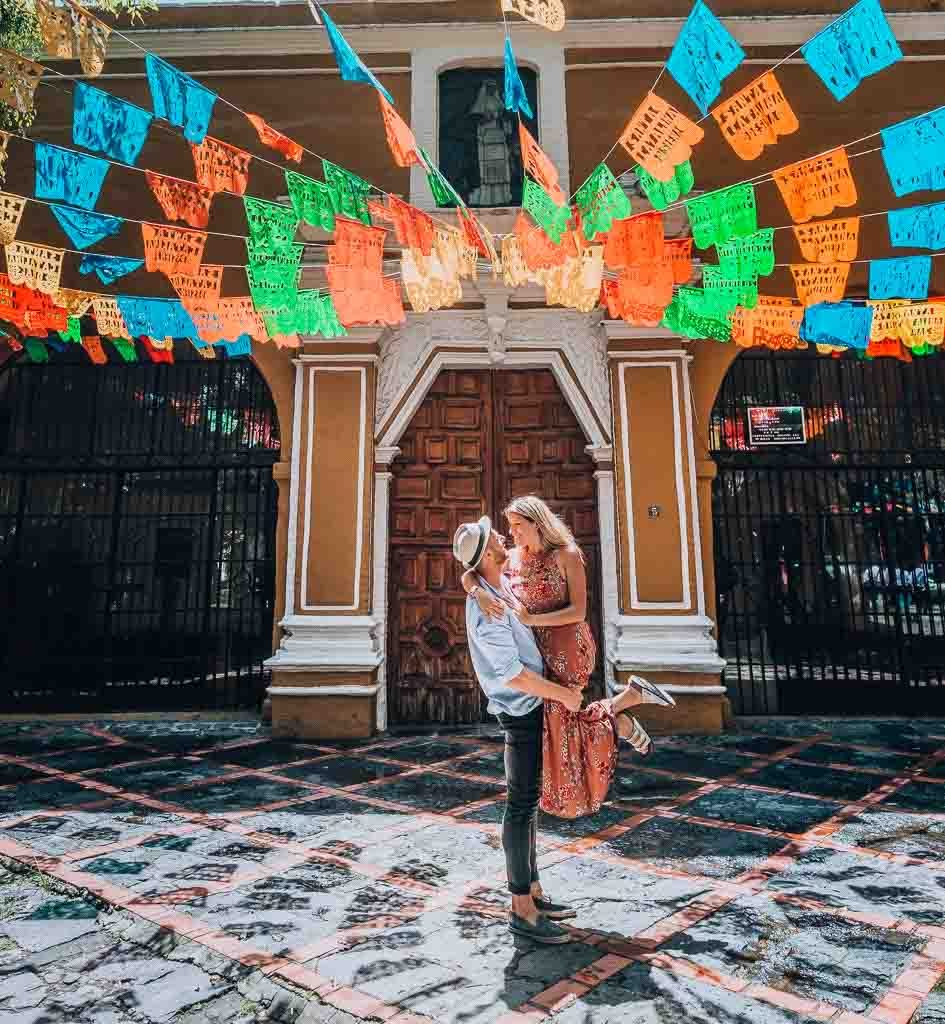 Mexico City Travel Guide: A man is liftung up his wife underneath a colorful roof outdoor