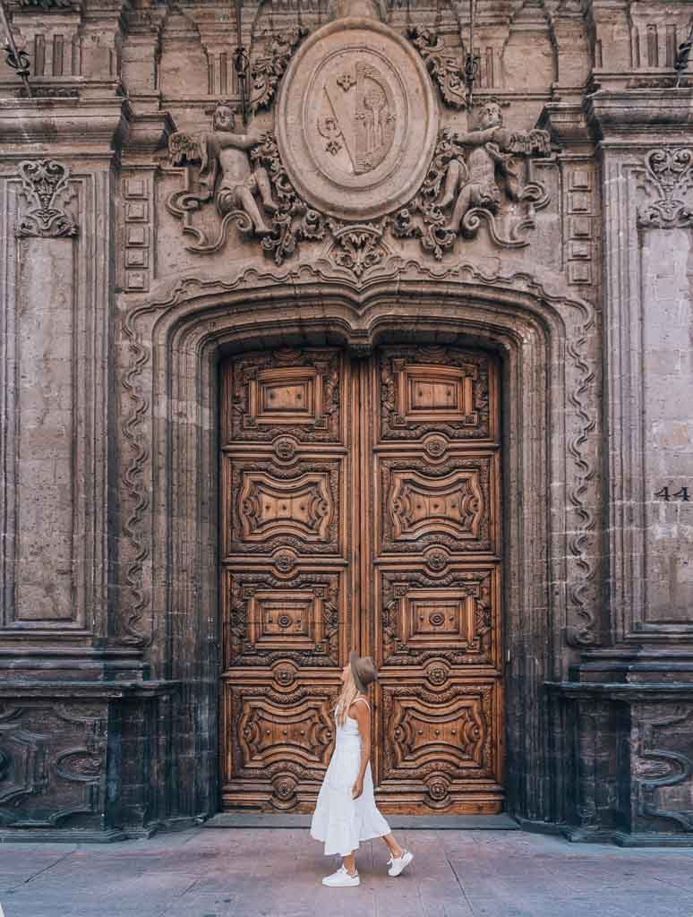 a girl is standing in front a huge wooden door which has beautiful ornaments