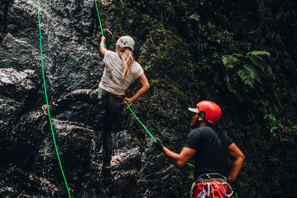Mindo Guide: a girl is doing canyoning with the help of a guide
