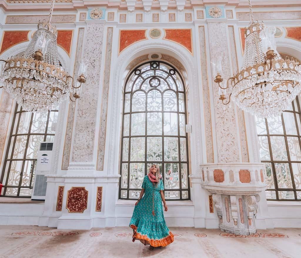 a girl is standing in the inside of the Ortaköy mosque where are beautiful chandeliers hanging