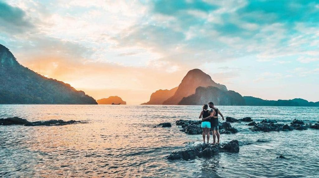 A couple is enjoying together a beautiful sunset.