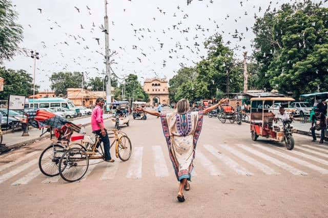 Tips for women traveling in India. A girl in a colorful dress standing in the middle of a street in India while a bycicle rikshaw rider is looking at her many pigeons are flying above and in front of her.